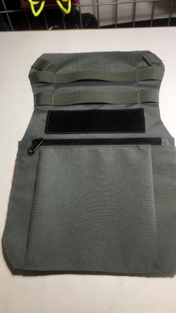 A velcro panel and zippered front pocket on this beavertail